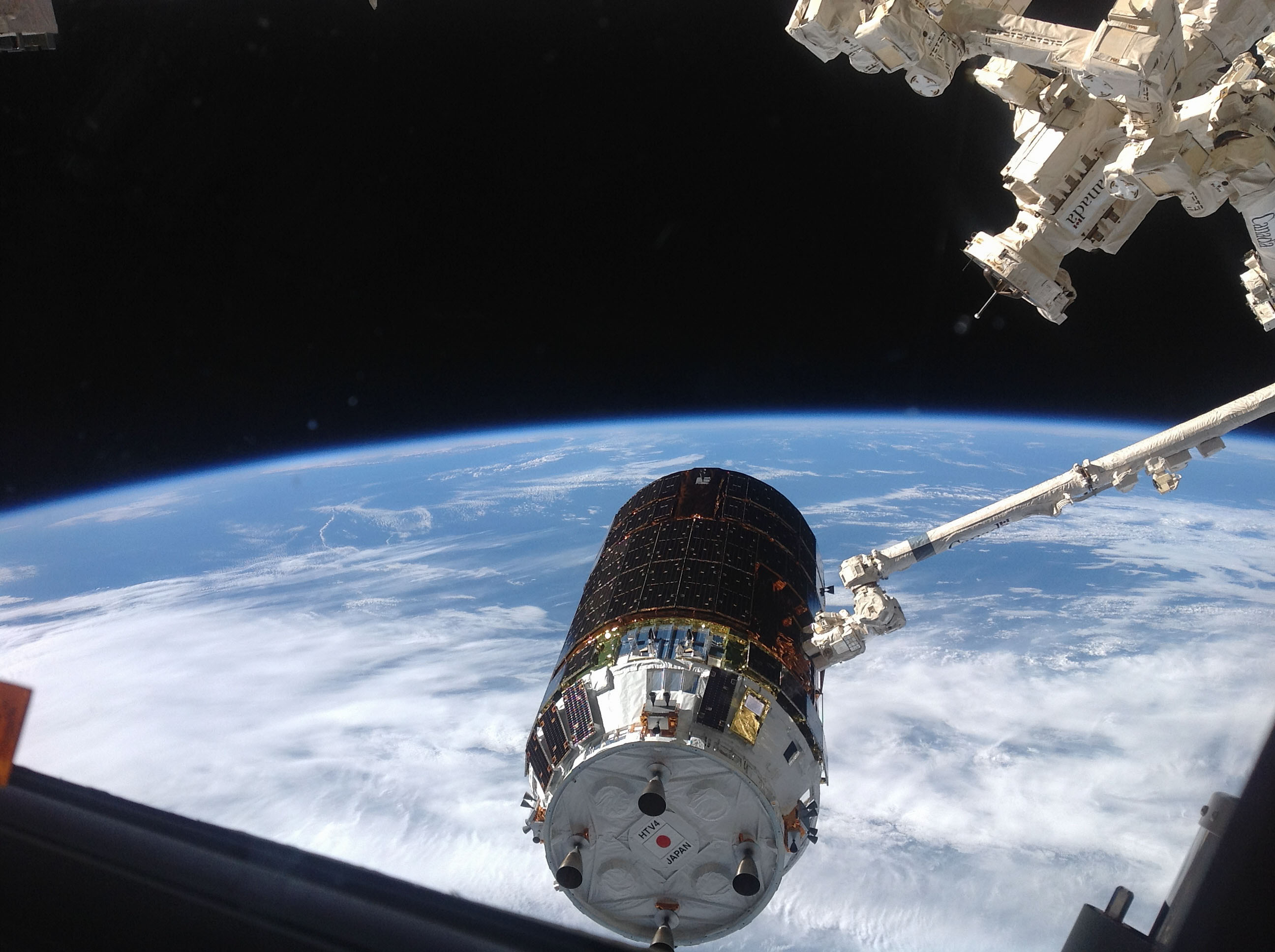 "The International Space Station's Canadarm2 grapples the unpiloted Japanese ""Kounotori"" H-II Transfer Vehicle-4 (HTV-4) as it approaches the station. Image Credit: NASA"