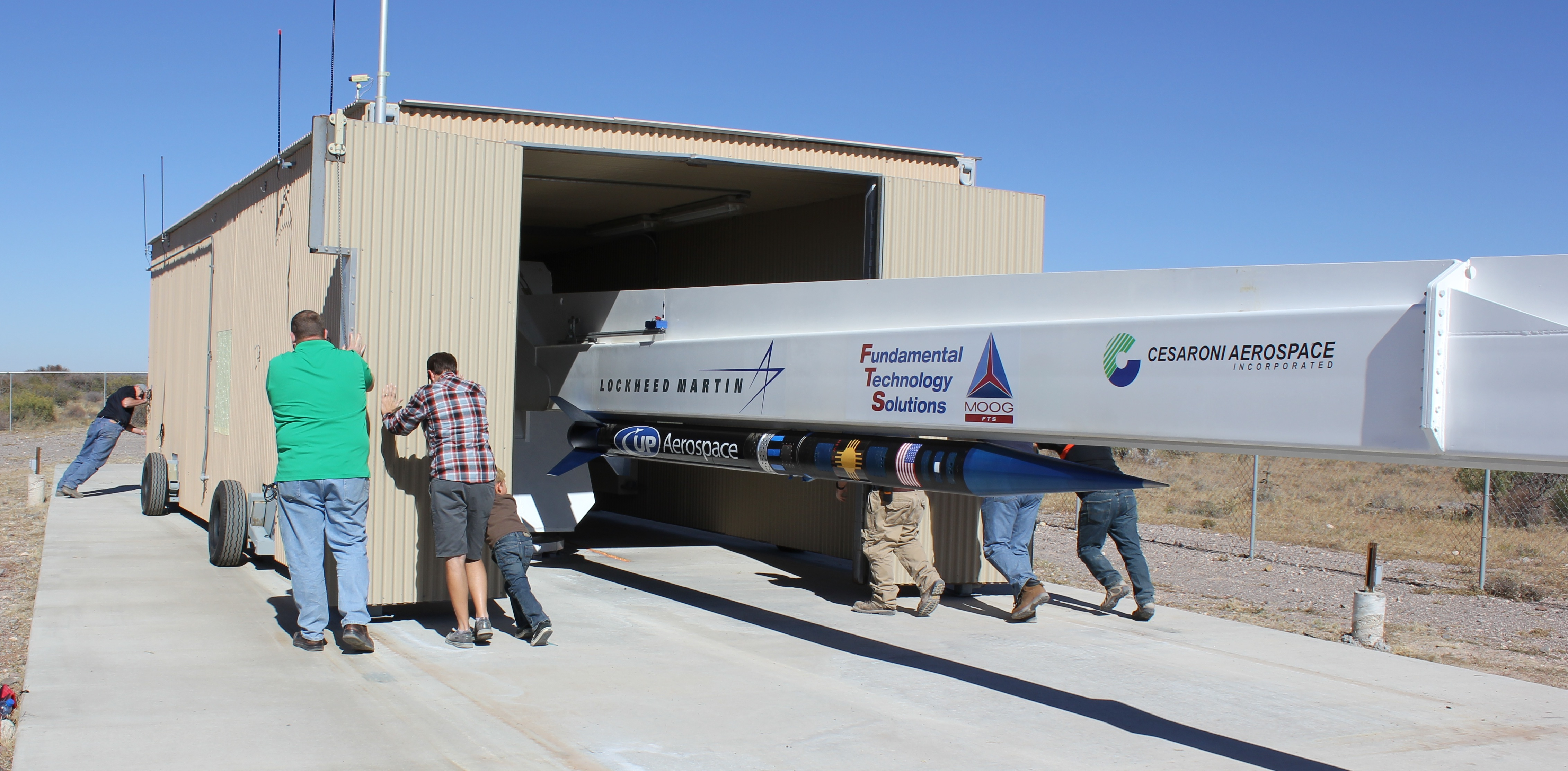 Members of the UP Aerospace ground grew roll back the moveable garage and payload integration facility to expose the launcher with the SL-8 sounding rocket mounted underneath. (NASA / Paul De Leon)