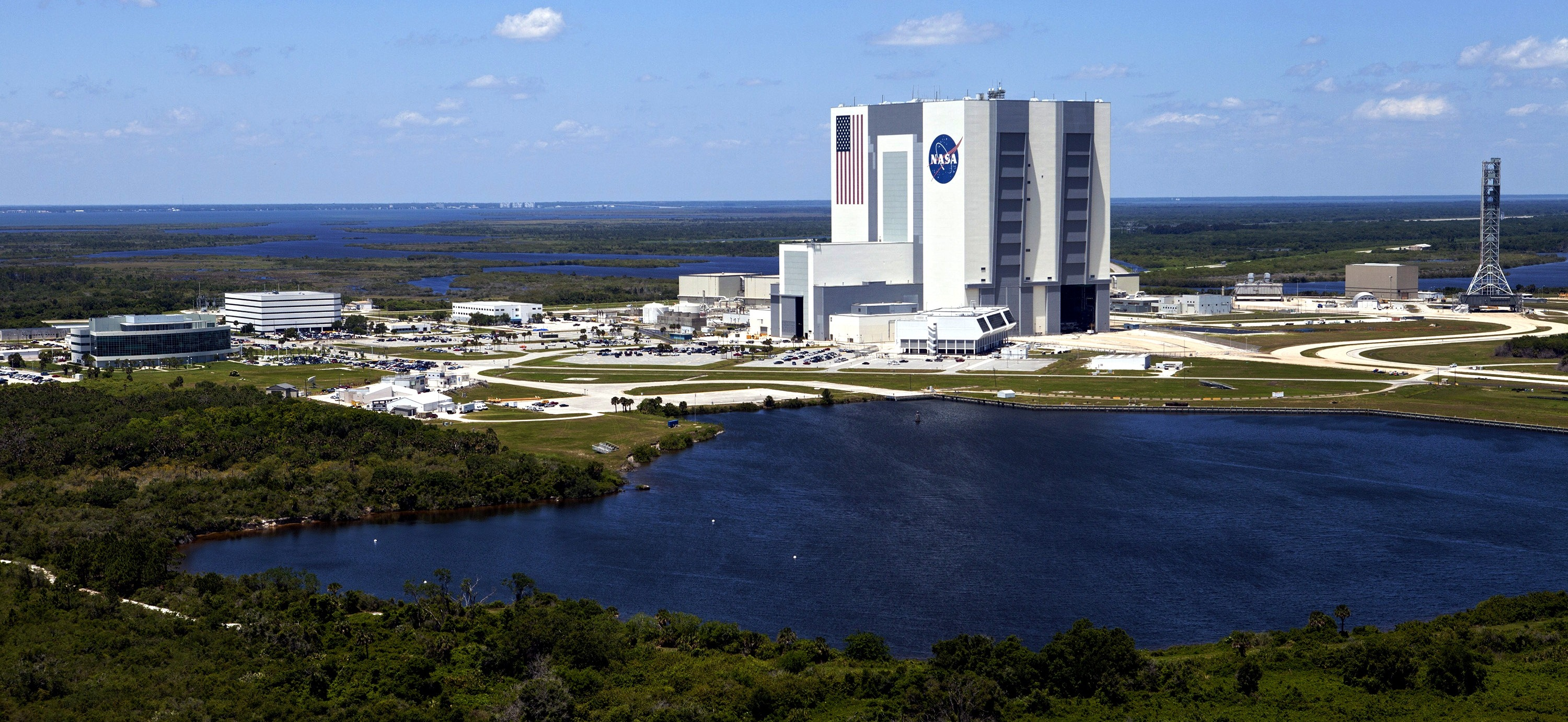 This aerial view shows the Vehicle Assembly Building, or VAB, and other buildings in the Launch Complex 39 area at NASA's Kennedy Space Center on May 6, 2013. The Launch Control Center is in front of the VAB. To the right is the mobile launcher that will be used to transport NASA's Space Launch System rocket and the Orion crew capsule to Launch Pad 39B. Upgrades are underway at Pad B and other facilities in the Launch Complex 39 area. The Ground Systems Development and Operations Program office at Kennedy is leading the center's transformation from a historically government-only launch complex to a spaceport that can safely handle a variety of rockets and spacecraft. Image Credit: NASA/Kim Shiflett