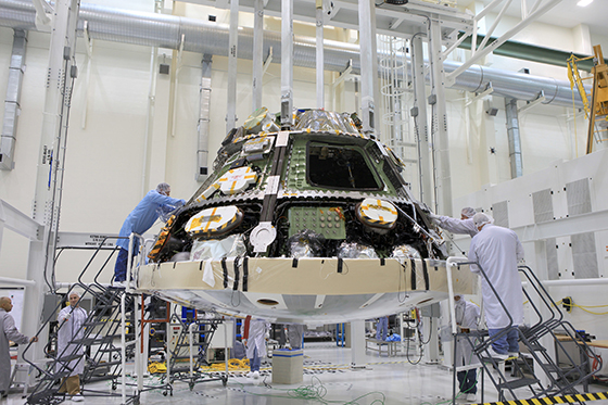 Lockheed Martin technicians and engineers attach the heat shield to the Orion crew module inside the Operations and Checkout Building high bay at NASA's Kennedy Space Center in Florida. Photo credit: NASA/Daniel Casper