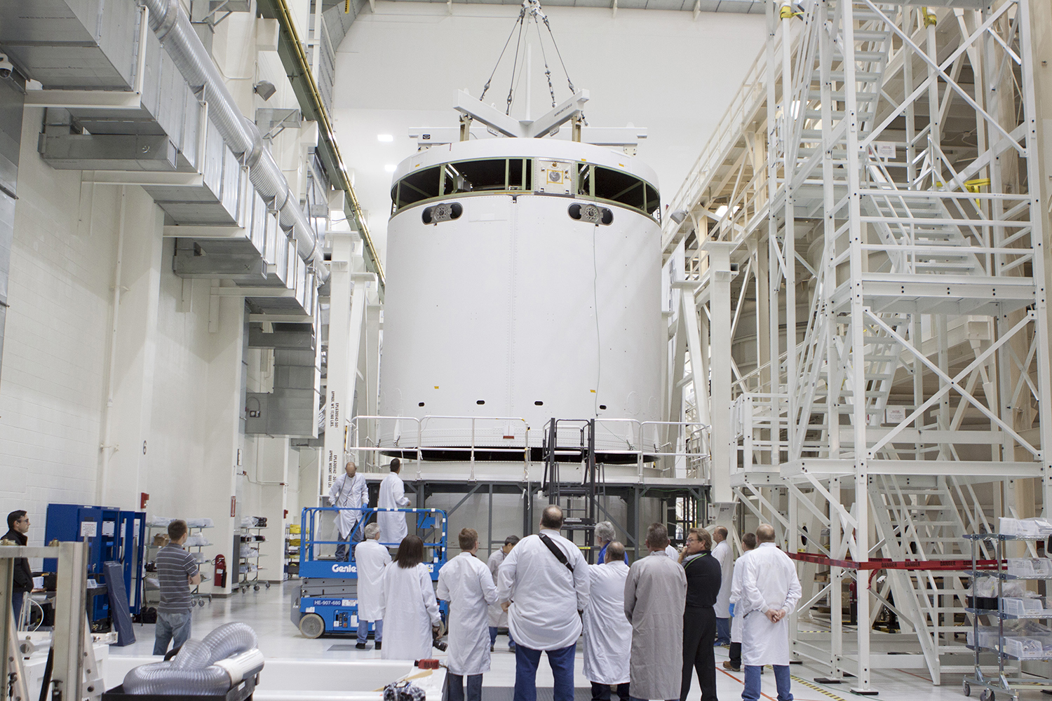 Inside the Operations and Checkout Building high bay at NASA's Kennedy Space Center in Florida, NASA and Lockheed Martin technicians and engineers monitor the progress as a crane is used to lift the Orion service module from a test stand and move it to the Final Assembly and System Testing, or FAST, cell further down the aisle
