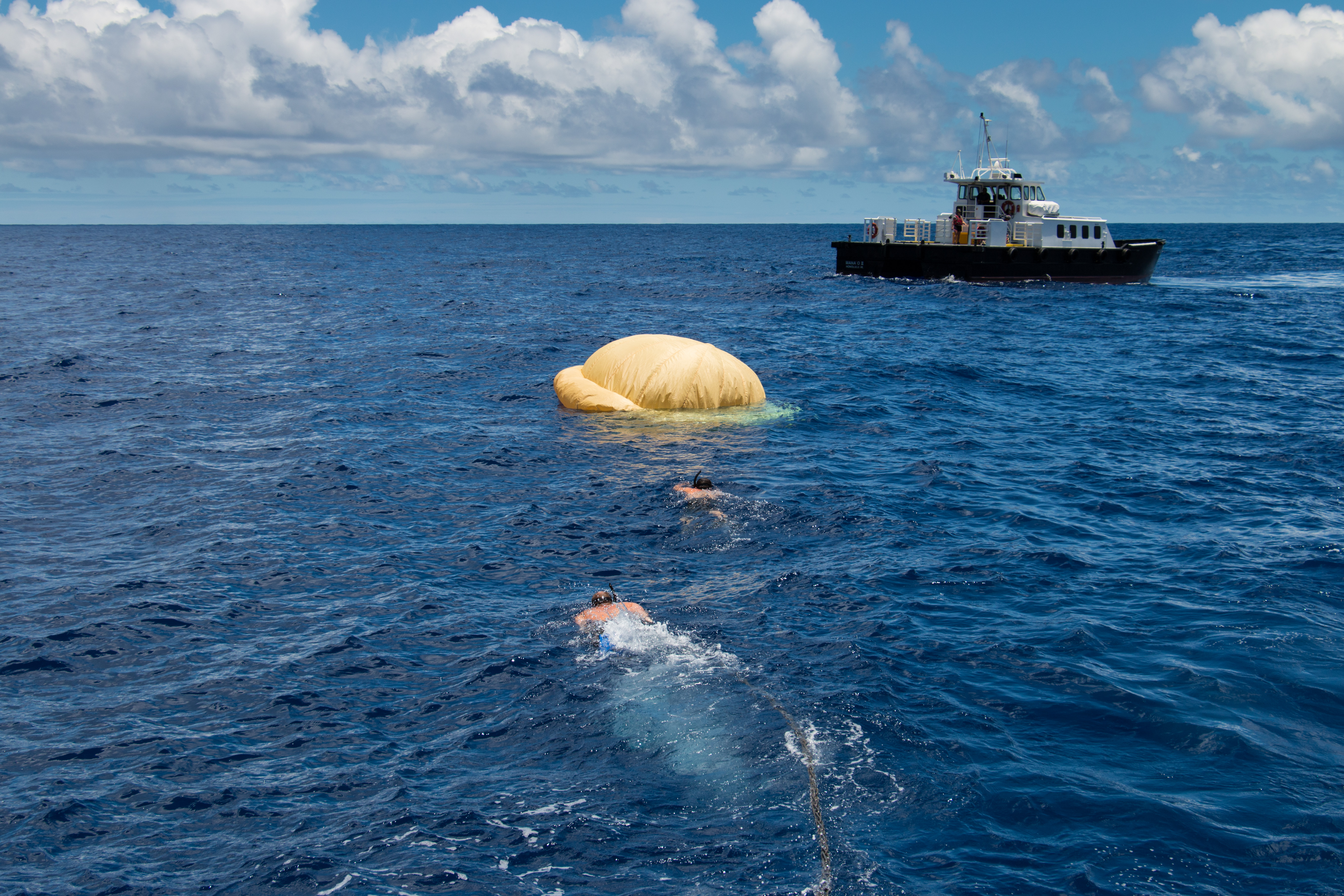 Two members of the Navy's Explosive Ordinance Disposal team swim towards the pilot ballute (a combination balloon and parachute used for braking at high altitudes and speeds) that was used to deploy the parachute. The recovery vessel Mana'o II is in the background. Image Credit: NASA/JPL-Caltech