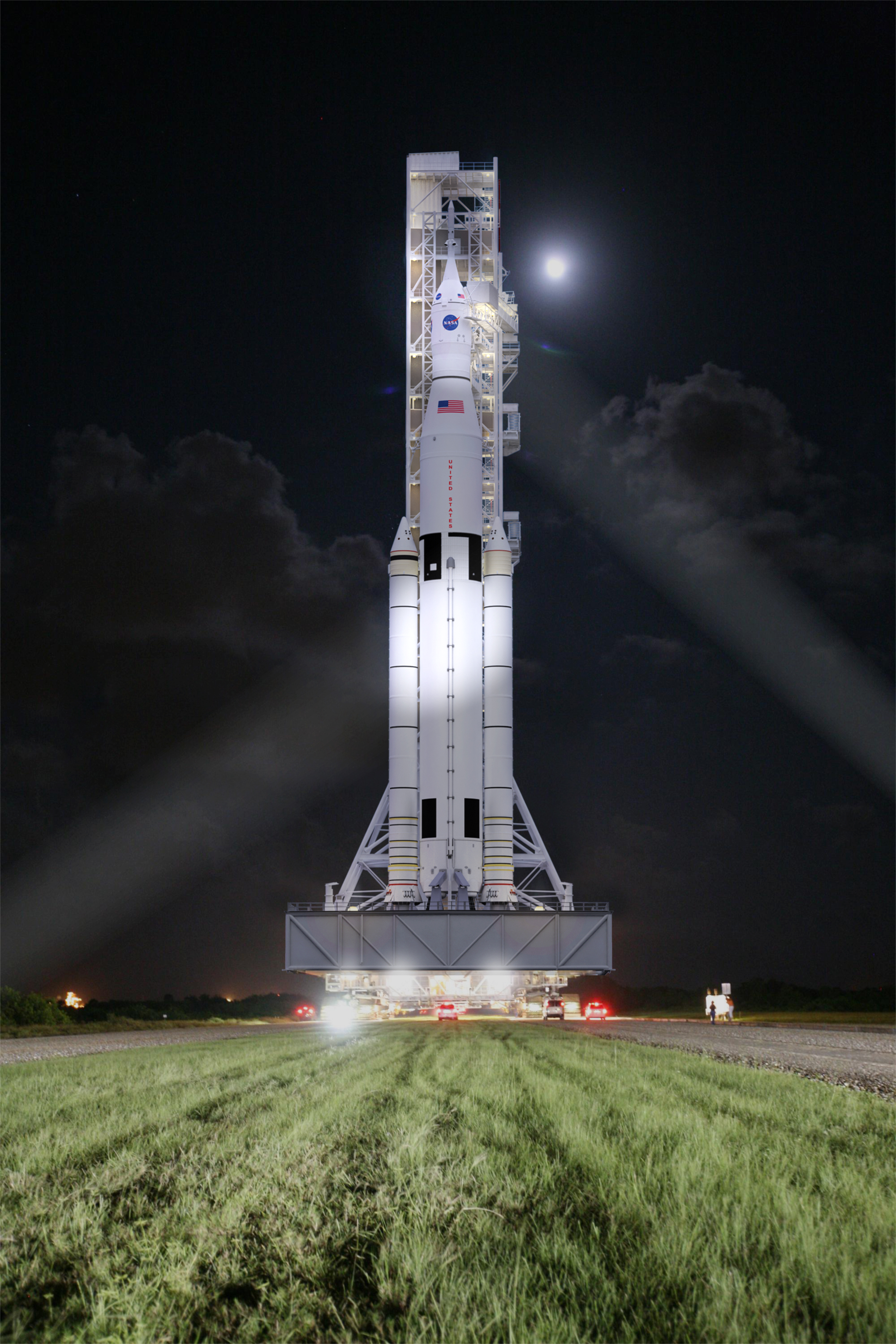 This artist concept shows NASA's Space Launch System, or SLS, rolling to a launchpad at Kennedy Space Center at night. SLS will be the most powerful rocket in history, and the flexible, evolvable design of this advanced, heavy-lift launch vehicle will meet a variety of crew and cargo mission needs. Image Credit: NASA/MSFC