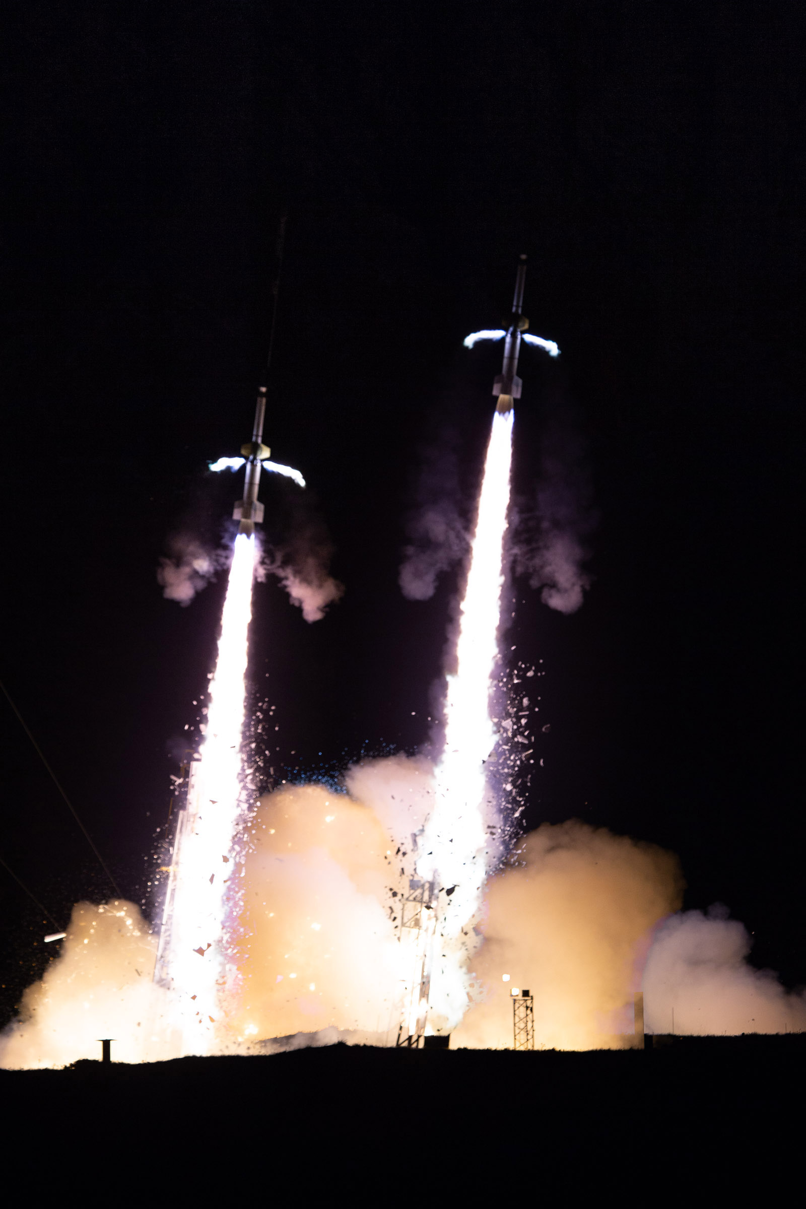 This composite photo shows The Twin Rockets to Investigate Cusp Electrodynamics or TRICE-2 that were launched at 3:26 and 3:28 a.m. EST, Dec. 8, 2018, from the Andoya Space Center in Andenes, Norway. The motors firing on the sides of the first stages spin the rocket to assist in stabilization during flight. The mission is one of nine international missions through January 2020  called the Grand Challenge Initiative - Cusp.  Credit: NASA/Jamie Adkins